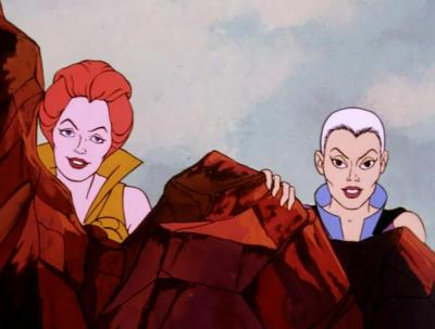 Teela & Evil-Lyn hiding behind a rock without their headgear and smiling